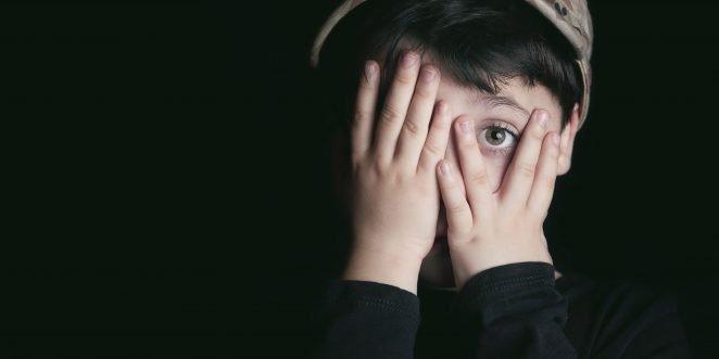 Kind hält sich die Hände vor das gesicht