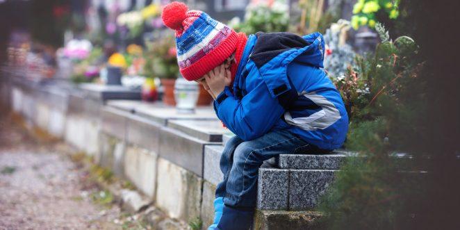 kleiner Junge sitzt traurig auf einem Friedhof