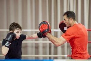 Kind arbeitet mit seinem Boxtrainer