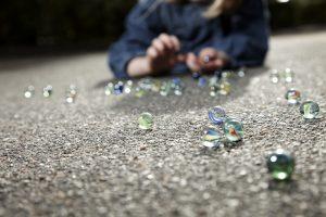 ein kind spielt mit murmeln