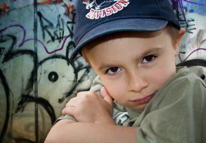 Kind sitzt vor einer mit Graffiti beschmierten Wand