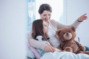 Mutter Kind und Teddy im Bett