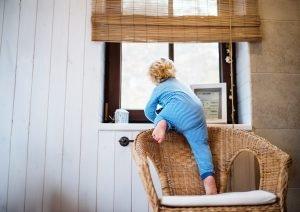 Kind klettert über Stuhl Richtung Fenster