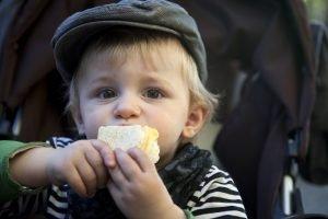 ein Kind hält ein Stück Brot in der Hand