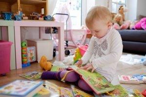 kleinkind haelt ein bilderbuch in den haenden