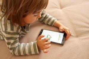 ein kind liegt mit einem smartphone auf dem bett