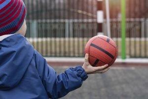 ein kind haelt einen handball in der hand