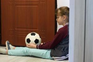 ein kind sitzt mit einem ball in der hand vor der tuer weil es hausarrest hat