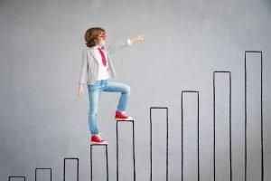 Kind steht auf imaginären Balken, die eine Karriereleiter symbolisieren