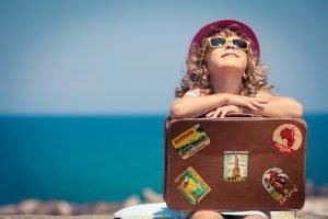 ein kind sitzt mit einem koffer am strand