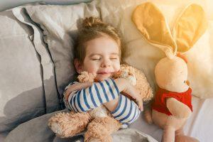 Kind liegt mit einem Kuscheltier im Bett