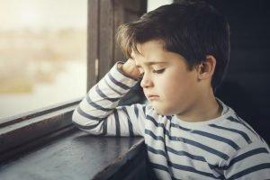 Außenseiter-Kind traurig an fenster