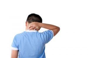 ein kind mit nackenschmerzen greift sich in den nacken