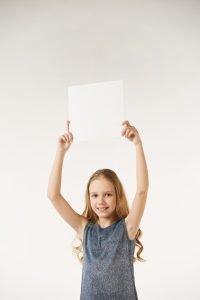 ein kind haelt ein weisses blatt papier in die luft