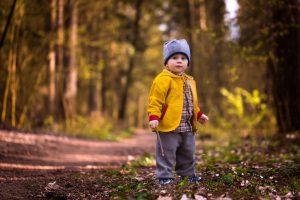 Kind mit offener jacke im wald
