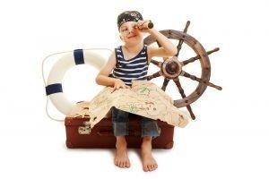 ein als pirat verkleidetes kind haelt eine schatzkarte in den haenden