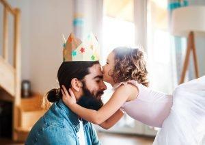 ein kind setzt ihrem vater eine selbst gebastelte krone auf