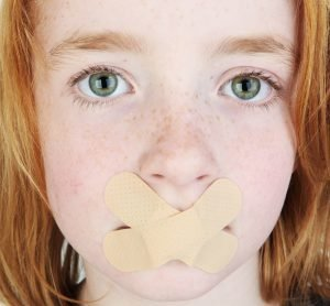 Kind mit zugeklebten Mund