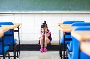 trauriges maedchen sitzt alleine im klassenraum