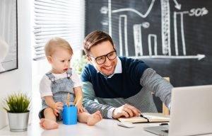 Kind schaut interessiert Vater zu wie er den Computer bedient.