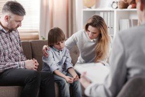 Kind redet nicht und sitzt mit Eltern, die sich Sorgen, auf einer Couch