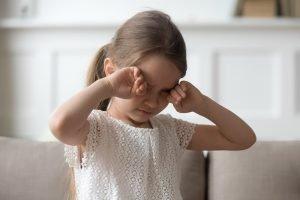 müdes Mädchen reibt sich die Augen vor Müdigkeit