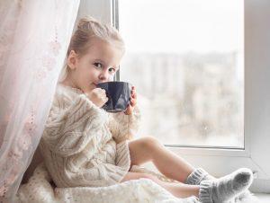 kleines maedchen trinkt einen tee am fenster