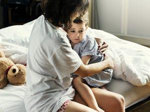 Mutter tröstet ihren kleinen Jungen bei einem Nachtschreck