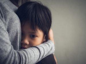 Kind wird von Person umarmt