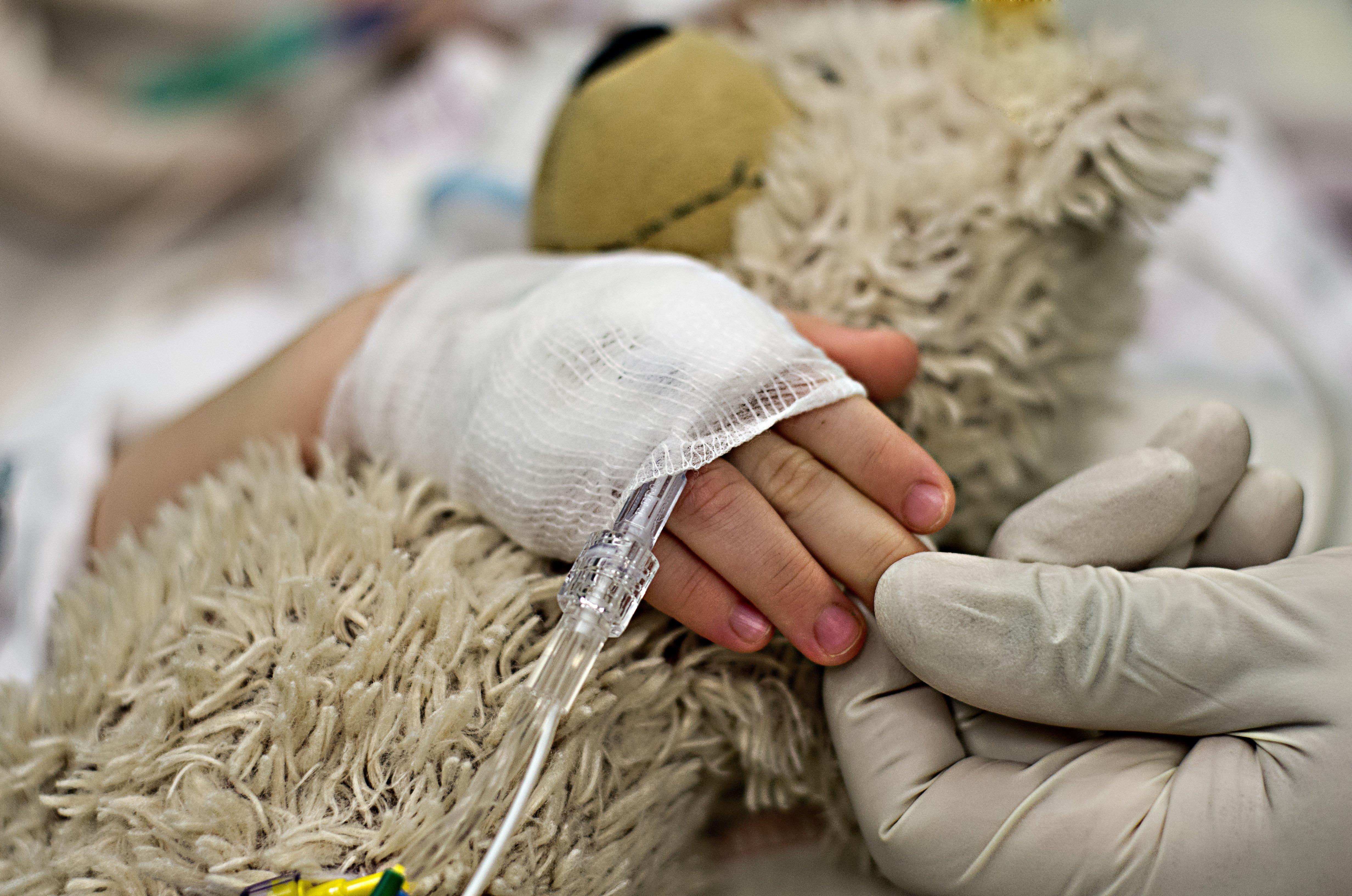 Teddybär wird von Kind im Krankenhaus umklammert