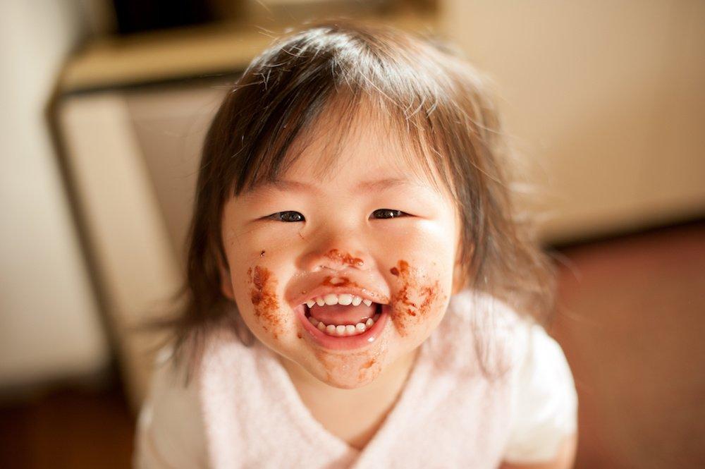 Kind lacht und hat Essen im Gesicht