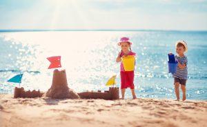 Kinder bauen eine Sandburg am Strand