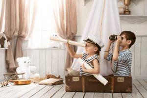zwei kinder sitzen in einem koffer und erleben ein mikroabenteuer als seefahrer