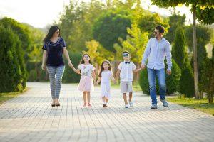 Eltern mit drei Kindern laufen glücklich über die Straße