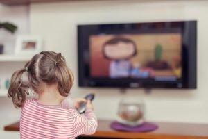 kleines Mädchen schaut ein Kinderprogramm im Fernsehen