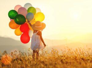 ein kind mit mehreren ballons in der hand