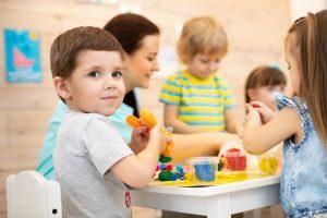kinder mit einer erzieherin im kindergarten