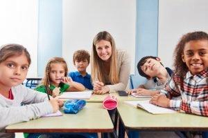 schulkinder sitzen mit ihrer lehrerin gemeinsam am tisch