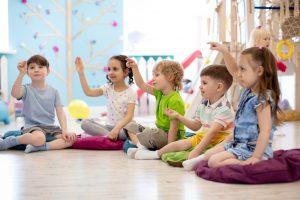 kindergartenkinder sitzen in einem kreis beisammen