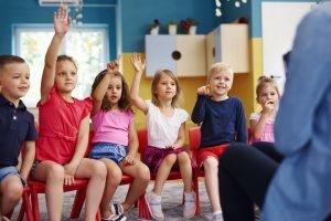 kinder sitzen in der ersten klasse vor der lehrerin