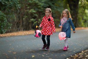 Kinder gehen mit einer Laterne die Straße entlang