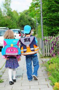 Kinder mit Schulranzen auf Gehweg