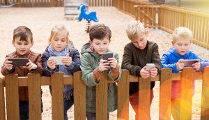 fuenf kinder stehen an einem zaun und schauen auf ihre smartphones