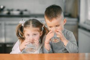 ein junge und ein maedchen trinken wasser