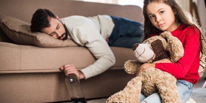 alkoholisierter Vater liegt auf Couch, trauriges Kind sitzt davor