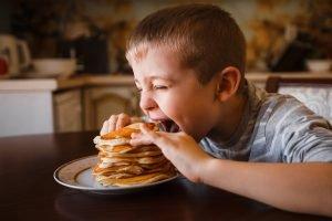 Kind isst stapel eierkuchen