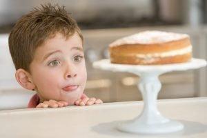 Kind steht mit Appetit vor einem Kuchen