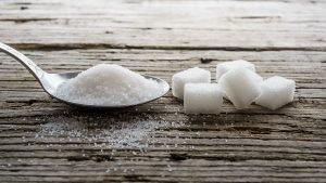 Löffel mit Zucker daneben Zuckerwürfel