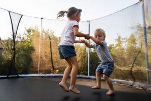 Kinder springen zusammen Trampolin