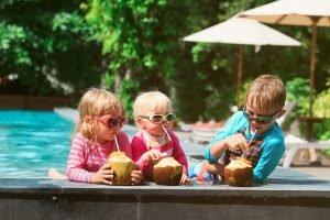Kinder trinken Cocktails aus Kokusnüssen am Pool